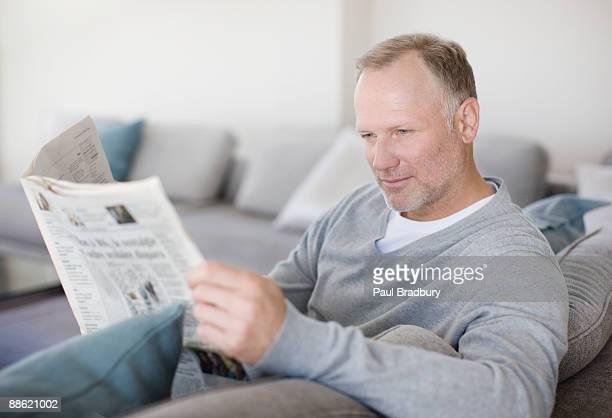 Mann sitzt auf der Couch bei der Lektüre der Tageszeitung