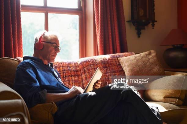 Man sitting on sofa using digital tablet