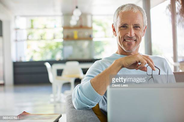 man sitting on sofa using laptop - ein mann allein stock-fotos und bilder