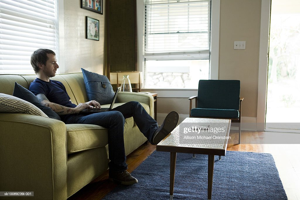 Man sitting on sofa using laptop : Stockfoto