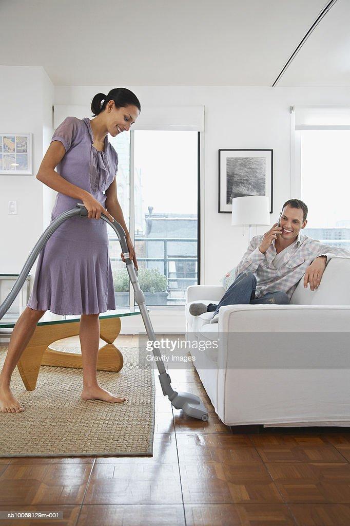 Man sitting on sofa using mobile phone, woman vacuuming floor : Stockfoto
