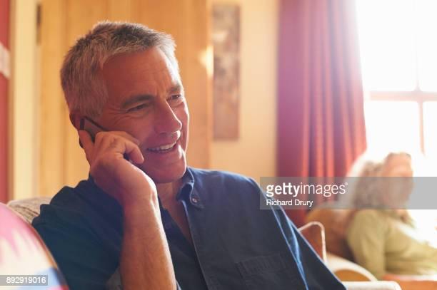 Man sitting on sofa using phone