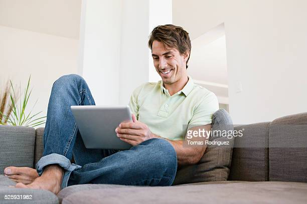 man sitting on sofa using tablet pc - one mid adult man only stock pictures, royalty-free photos & images