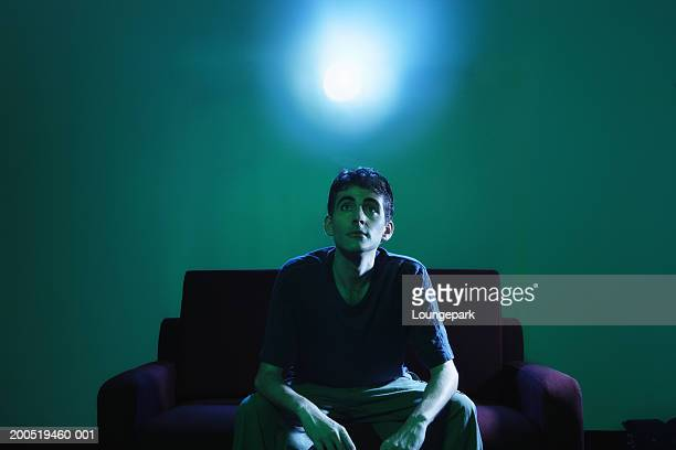 man sitting on sofa watching television - hypnose photos et images de collection