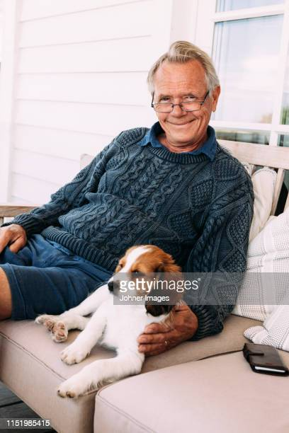 man sitting on sofa with dog - domestic animals stock pictures, royalty-free photos & images