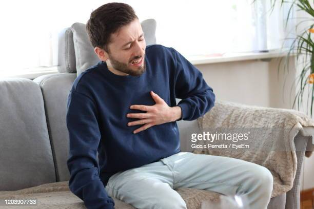 man sitting on sofa with hand on chest at home - heart attack stock pictures, royalty-free photos & images