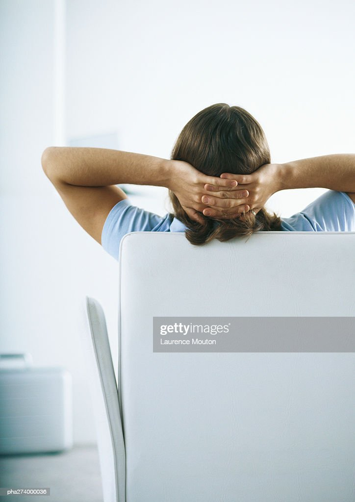 Man sitting on sofa with hands behind head, rear view : Stockfoto
