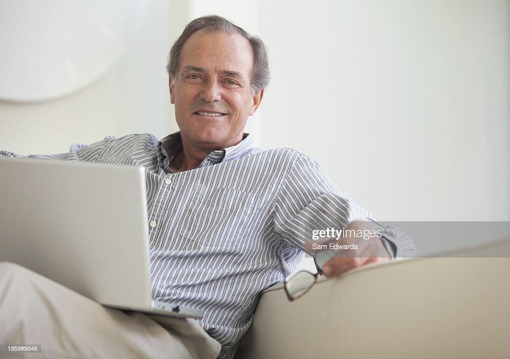 Man sitting on sofa with laptop : Stock Photo