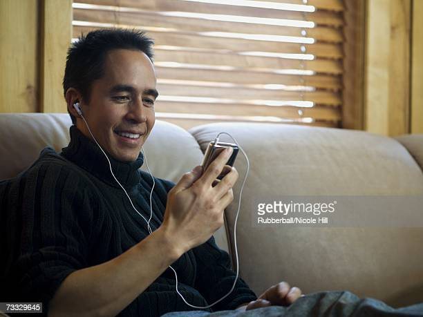 Man sitting on sofa with mp3 player listening to music smiling