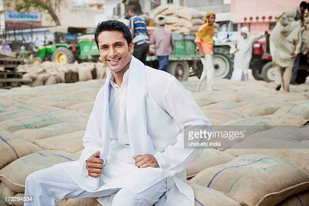man sitting on stack of wheat sacks in a grain market, anaj mandi, sohna, gurgaon, haryana, india - loading stock pictures, royalty-free photos & images