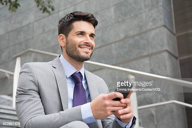 Man sitting on stairs and using smart phone