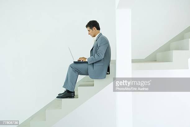 Man sitting on stairs, using laptop