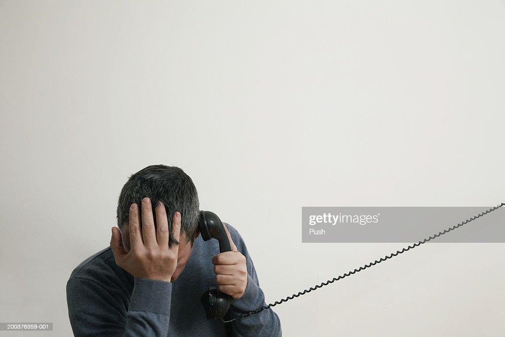 Man sitting on stairs using telephone, hand to head : Stock Photo