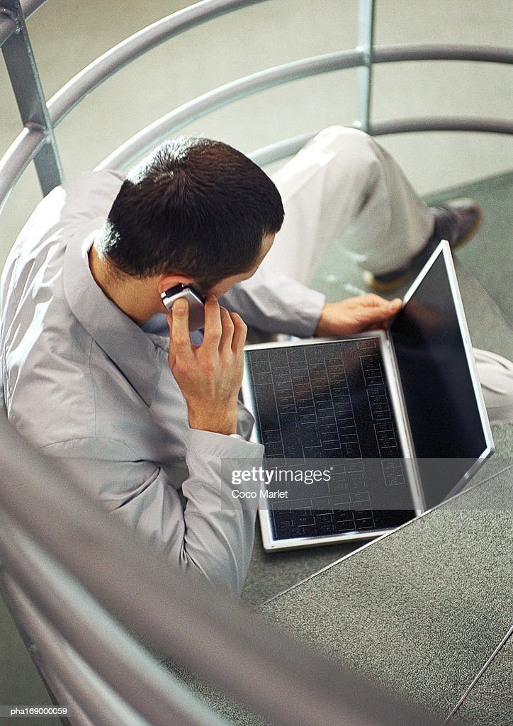 Man sitting on stairs with cell phone and laptop computer, high angle view : Stockfoto