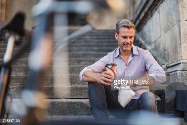 Man sitting on stairs with takeaway coffee in the city checking the time
