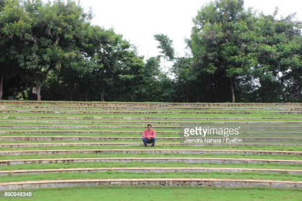 Man Sitting On Steps In Park Against Sky