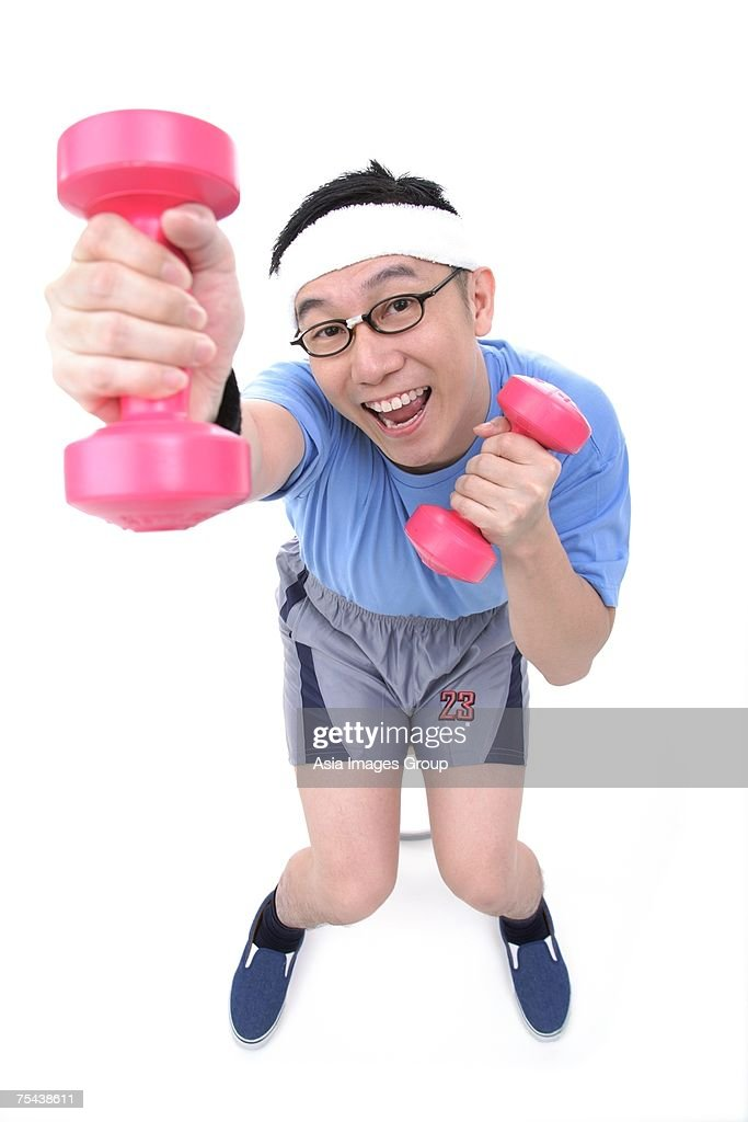 man sitting on stool using dumbbells stock photo getty images