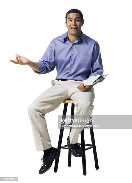 Man sitting on stool with clipboard gesturing