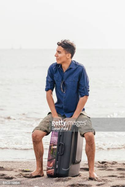 Man Sitting On Suitcase On The Beach