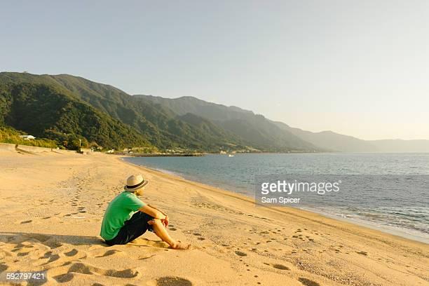 Man sitting on sunset beach