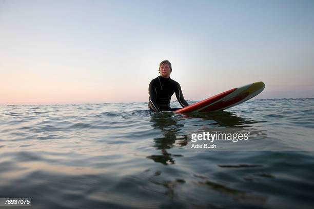 man sitting on surfboard in the water. - surfboard stock pictures, royalty-free photos & images
