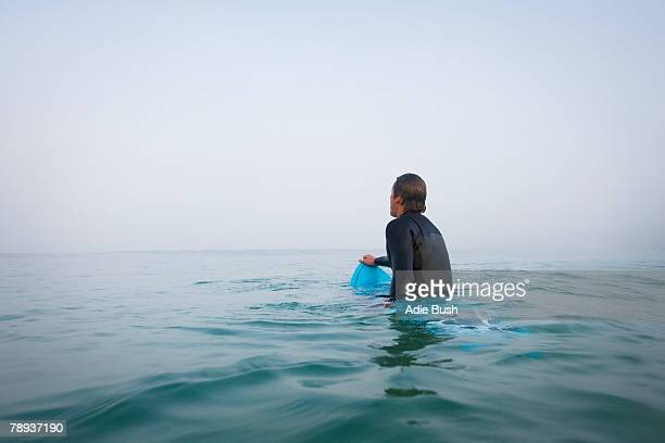 Man sitting on surfboard in the water.