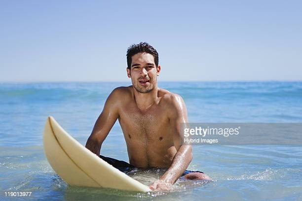 Man sitting on surfboard in water