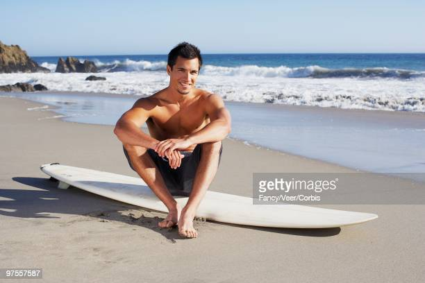 man sitting on surfboard - calzoncini da bagno foto e immagini stock