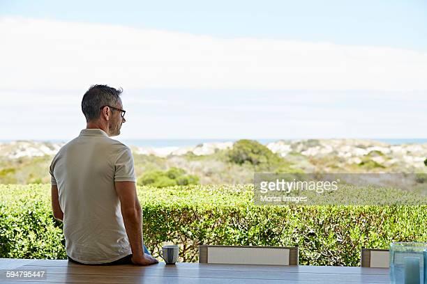 Man sitting on table against landscape