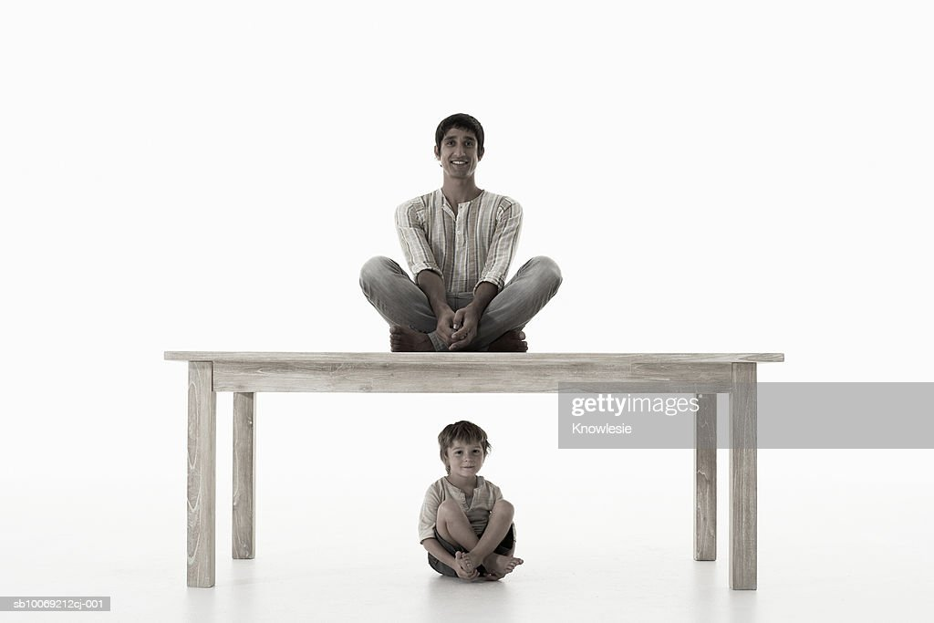 Man sitting on table, boy (4-5 years) sitting below, against white background, portrait : Stockfoto