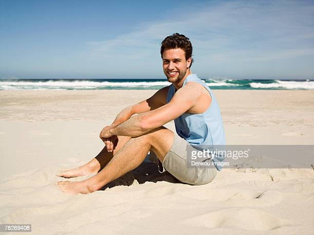 a man sitting on the beach. - vest stock pictures, royalty-free photos & images