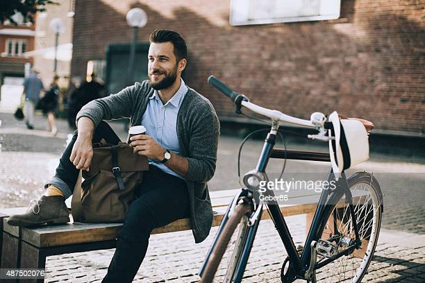 Man sitting on the bench and enjoying coffee