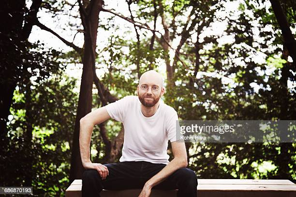man sitting on the bench and relaxed in the forest - hand on knee stock pictures, royalty-free photos & images