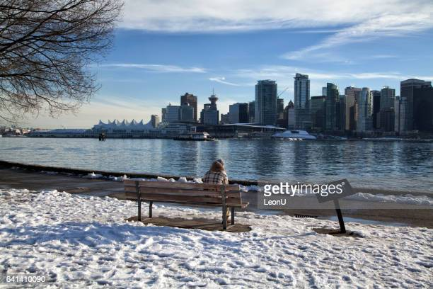 man sitting on the bench enjoying the vancouver skyline - stanley park stock photos and pictures
