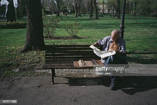 Man sitting on the bench waiting for chess partner, reading reading newspapers. Kalemagdan, Belgrade, Serbia 2012