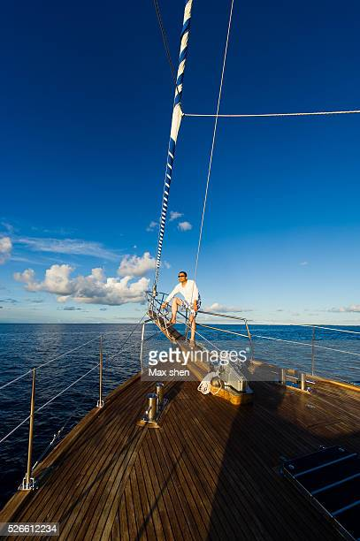 Man sitting on the bow of the sailing yacht