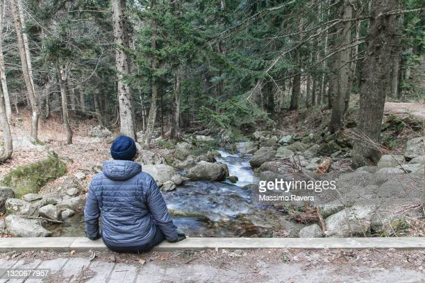 man sitting on the bridge looking at the river flowing. - generic location stock pictures, royalty-free photos & images