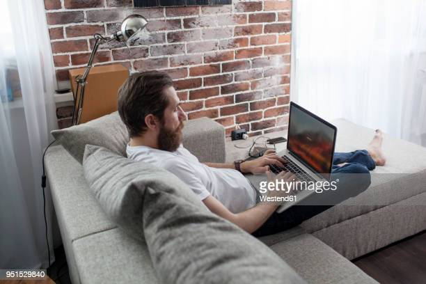 man sitting on the couch at home using laptop - log on stock photos and pictures