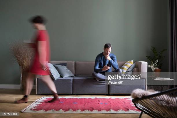 Man sitting on the couch in the living room while his girlfriend passing in the foreground
