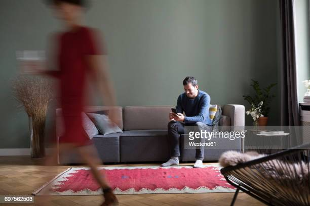 man sitting on the couch in the living room while his girlfriend passing in the foreground - focus on background stock pictures, royalty-free photos & images