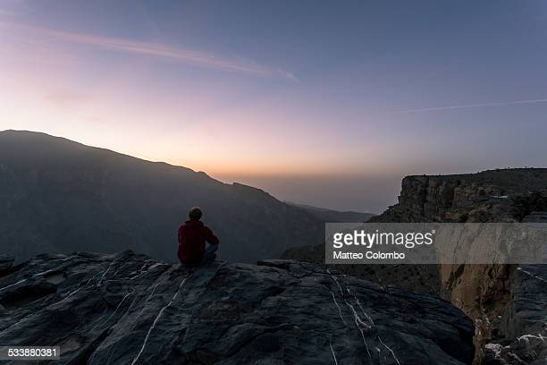 Man sitting on the edge of canyon at sunrise, Oman