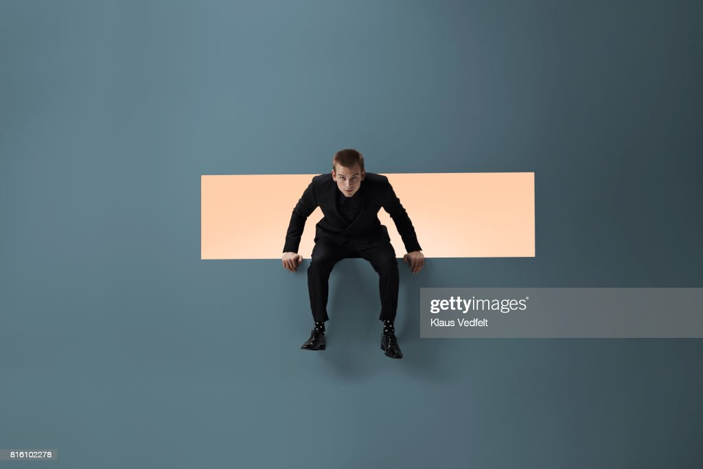 Man sitting on the edge of rectangular opening in coloured wall : Stock Photo
