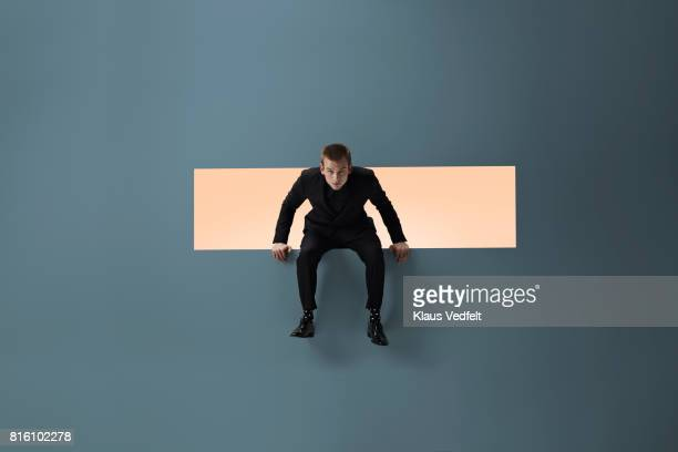 man sitting on the edge of rectangular opening in coloured wall - caucasian appearance stock pictures, royalty-free photos & images