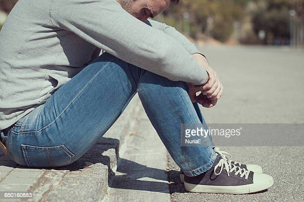Man sitting on the edge of the kerb
