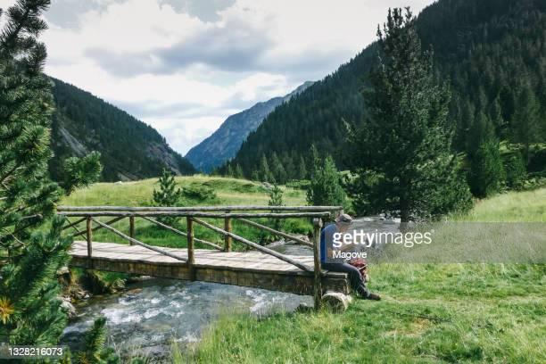 uomo seduto alla fine di un piccolo ponte letto in valle d'aosta, italia - valle d'aosta foto e immagini stock