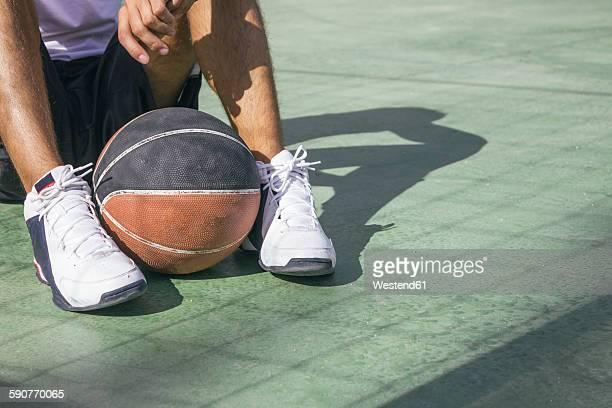 Man sitting on the floor with basketball ball between his feet