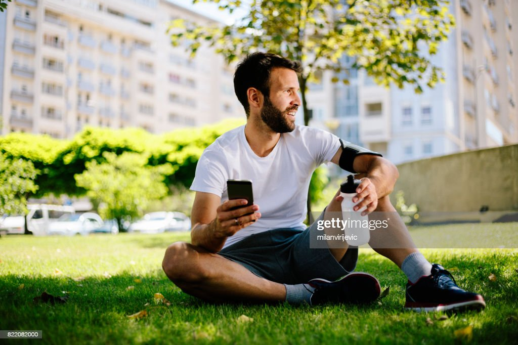 Man sitting on the grass and resting after training : Stock Photo