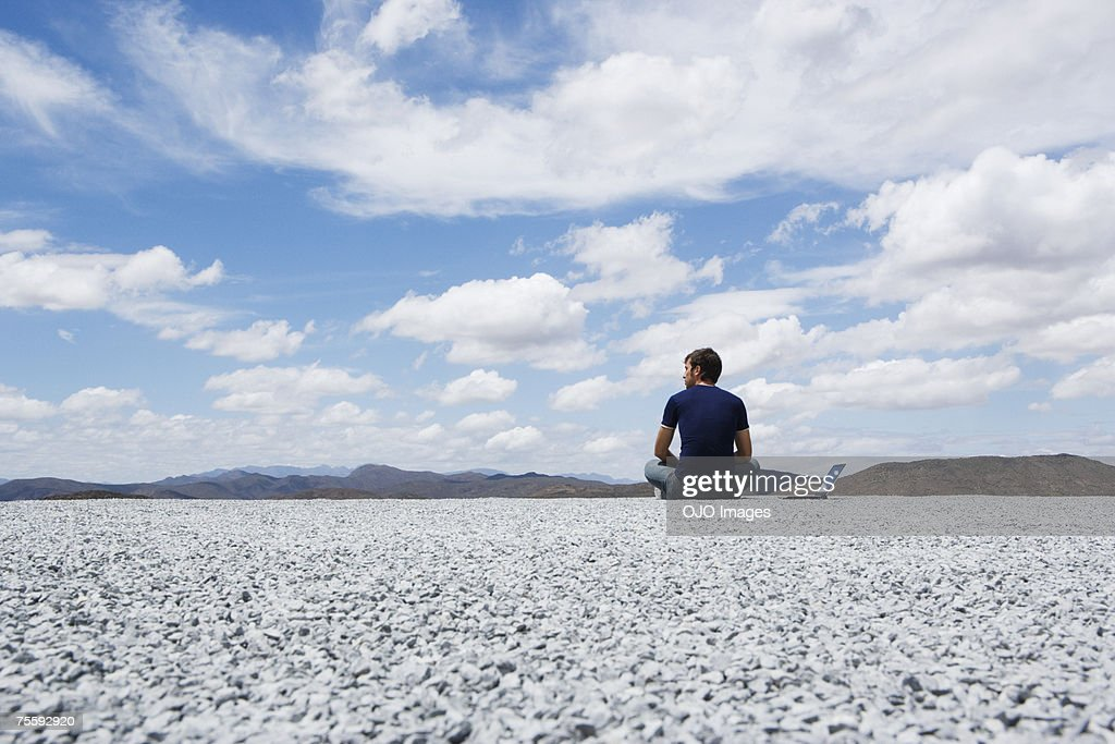 Man sitting on the ground with his laptop computer : Stock Photo