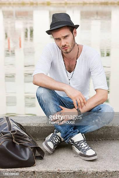 Man sitting on the ledge of a canal, Paris, Ile-de-France, France