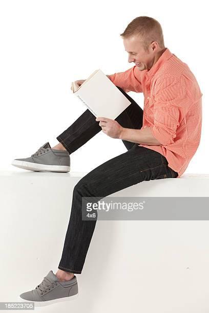 Mann sitzt auf dem ledge der Wand Sie ein Buch lesen